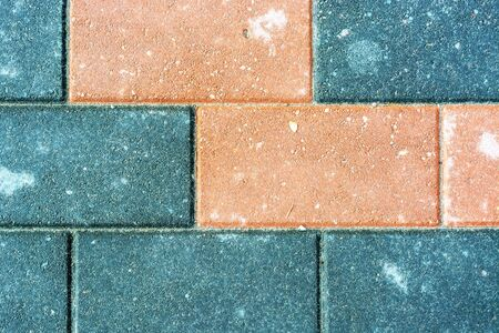 Fragment of a sidewalk lined with multicolored stone tiles for use as an abstract background and texture. Stockfoto - 129605130