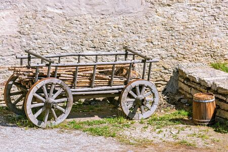 An old cart with wood and a wooden barrel stand near the old stone wall in the courtyard of the old castle in Rakvere.