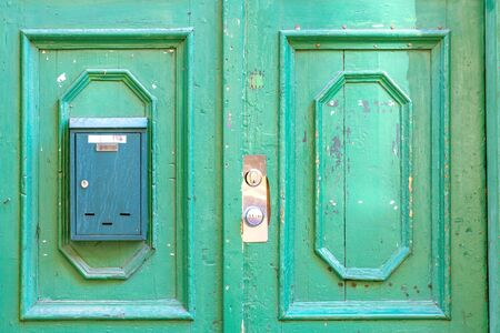 Fragment of old cracked wooden doors painted green with a mail box. From a series of doors to the world.