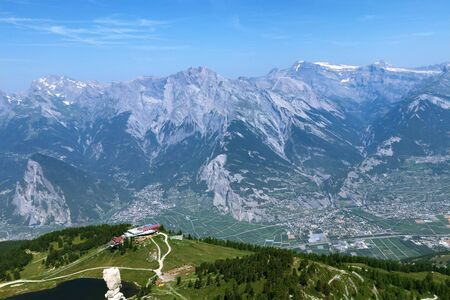 View of the Alpine mountains in Switzerland against the blue sky. In the foreground is a ski resort and in the valley is the city of Sion. 스톡 콘텐츠