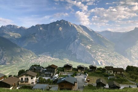 The village of Condemines in the mountains of Switzerland against the backdrop of the Alpine mountains and the sky with clouds. In the background in the valley is the city of Sion.