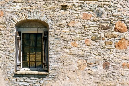 Window with arch, iron bars and wooden shutters on the fortress stone wall of the old castle in the city of Rakvere. From the window series of the world. 스톡 콘텐츠