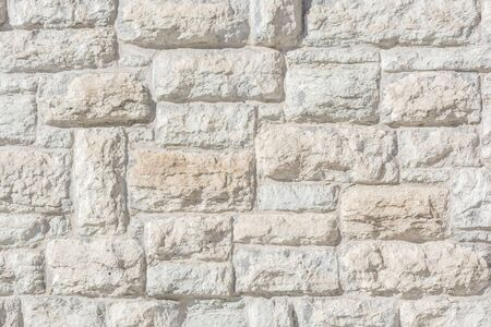Light fragment of an old limestone stone block wall for use as an abstract background and texture.