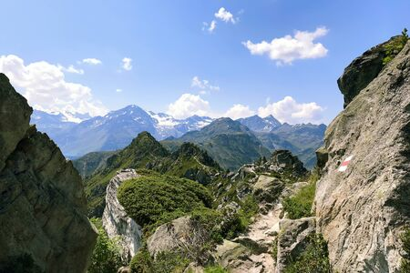 View of the Alpine mountains in Switzerland against a blue sky with white clouds on a bright Sunny day.