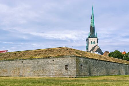 Spire of St. Olavs Church against the blue sky behind the city fortress wall of the old city of Tallinn.