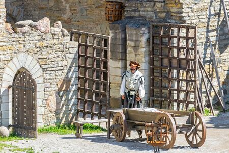 Rakvere, Estonia, June 28: A guard in national clothes stands at the gate in the courtyard of an old castle in Rakvere, June 28, 2019.
