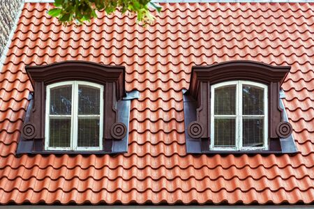 Two attic windows with white frames on the roof of red tiles. From a series of windows of the world.