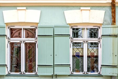 Two rectangular windows with white frames and green wooden shutters. From a series of windows of the world.