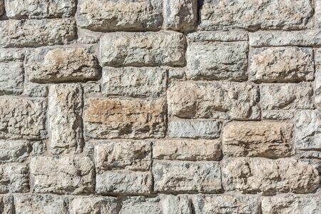 Dark fragment of an old limestone stone block wall for use as an abstract background and texture.