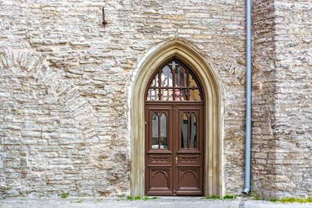 Wooden door brown with arched stained glass on the background of a stone wall. From a series of doors to the world.