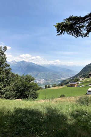 View of alpine meadows and mountains in Switzerland against a blue sky. In the background in the valley is the city of Sion.