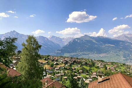 The village of Iserables in the mountains of Switzerland against the backdrop of the Alpine mountains and the sky with clouds. In the background in the valley is the city of Sion.