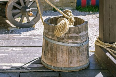 Wooden bucket with a rope stands on the lid of a well in the courtyard of a medieval castle in the Estonian city of Rakvere.
