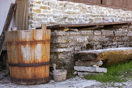 Old wooden tub with a rusty hoop stands near a stone wall in the courtyard of a medieval castle in the Estonian city of Rakvere.