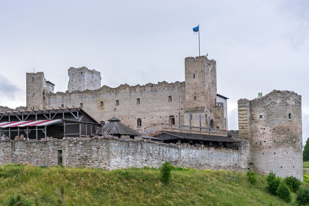 The ruins of the fortress walls of the old castle in the city of Rakvere with the Estonian flag on the tower against the cloudy sky.