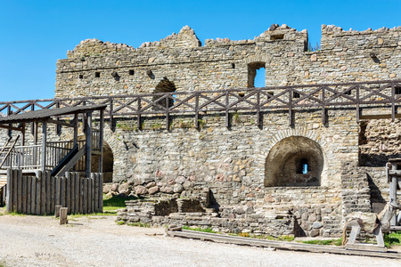 The inner courtyard of the old castle in the city of Rakvere with a view of the destroyed fortress walls against the blue sky.