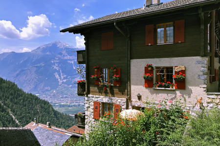 Chalet made of stone and wood with red wooden shutters and flowers on the Windows against the mountains in the Swiss Alps in the village of Condemines.