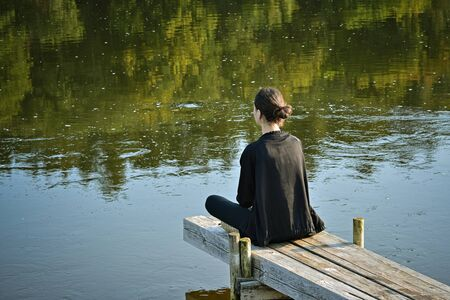 Young girl in a tracksuit and a black jacket sits cross-legged on walkways and holds a meditation session over the water surface of the river.