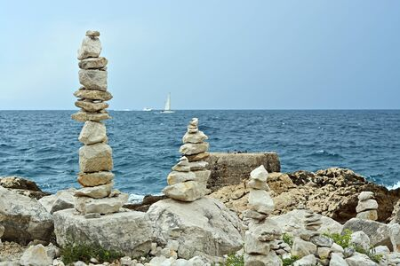 Cairns from stones on the rocky shore of the Adriatic in Croatia. Against the background of the blue sea, sky and sailboat, on the horizon. Banco de Imagens