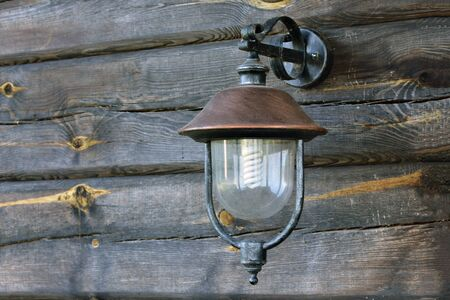Horizontal shot of a street lamp hanging on the wall from old weathered and grayed logs on a Lithuanian farm.