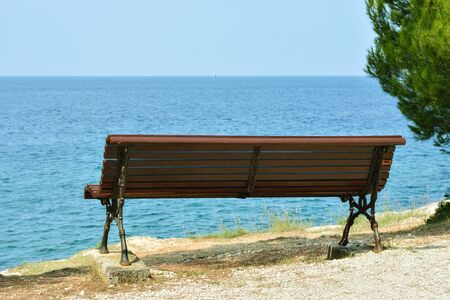 Bench stands on the seashore overlooking the sea horizon, for romantic communication of couples. The red island, the town of Rovinj in Croatia.