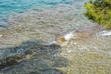 Small waves in the coastal part of a red island in Croatia off a rocky shore. A rocky bottom is visible through the transparent surface of the water. 스톡 콘텐츠