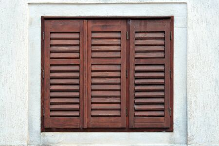 Window covered with brown wooden shutters. From a series of windows of the world. 스톡 콘텐츠