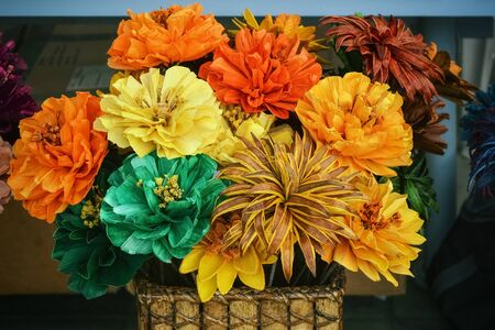 Bouquet of bright yellow, red and green flowers in a wicker basket.