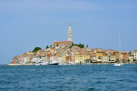 View of the old part of the city of Rovinj in Croatia against the blue sky, view of the promenade and the bay with yachts on a bright sunny day. 스톡 콘텐츠