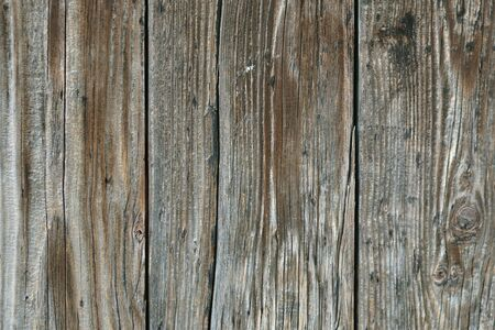 Fragment of the wall of old, weathered, gray with age boards. For use as an abstract background.
