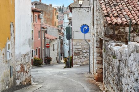 Going down a winding street of the old part of Rovinj in Croatia, with old stone houses.