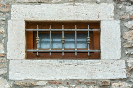 Small window with a brown wooden frame on the stone wall of the house, closed by a metal grill. From a series of windows of the world. Stockfoto