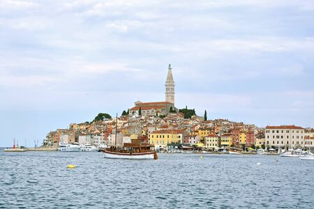 View of the old part of the city of Rovinj in Croatia against the blue sky, view of the promenade and the bay with yachts on a summer sunny day.