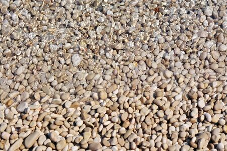 Beach pebbles, half covered with clear sea water. For use as an abstract background.