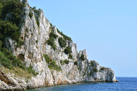 Steep rocky shore, overgrown with bushes, washed by the waters of the Adriatic sea against the blue sky. 版權商用圖片 - 134866836