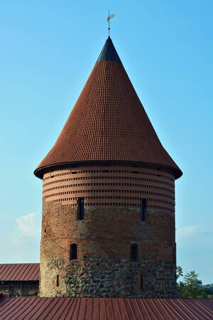 View of the top of an old round tower of red brick with a red tile dome, against the blue sky in the city of Kaunas, Lithuania. 版權商用圖片