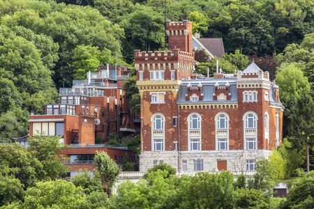 Red brick building with turrets, located on a slope covered with trees, in the city of Budapest in Hungary.