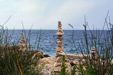 Stone pyramids on the rocky coast of the Adriatic sea in Croatia against the blue sea and sky are visible through the grass. Banco de Imagens