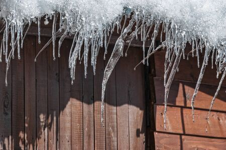 Icicles hanging from the roof of a house in the early morning on a Sunny spring day. Standard-Bild - 140647002