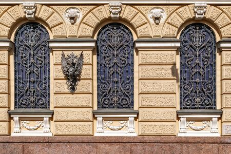 Three arched Windows with bars and bas- relief against a beige wall. From the series Windows of Saint Petersburg.