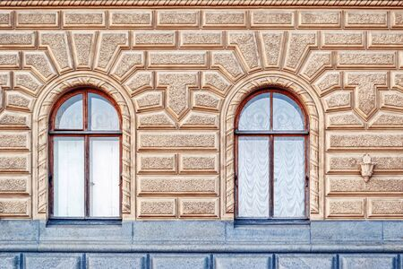 Two arched Windows on the background of beige walls with textured decorative plaster. From the series Windows of Saint Petersburg.