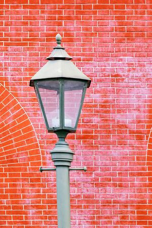 Fragment of a street lamp on a background of a red brick wall. 写真素材