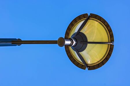 City street lamp, photographed from below, against a clear blue sky.