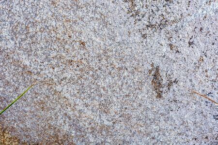 Rough rough surface of gray stone with reddish spots. For use as an abstract background and texture.