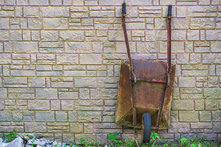 Old rusty iron wheelbarrow with one wheel, leaning against the wall of a country house.