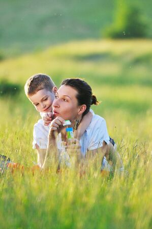 happy child and woman outdoor playing with soap bubble on meadow Stock Photo - 5288251