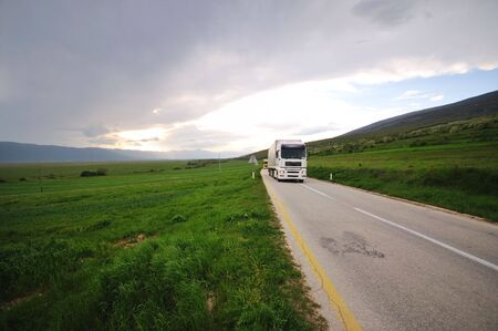haulage: big truck drive on long country road Stock Photo