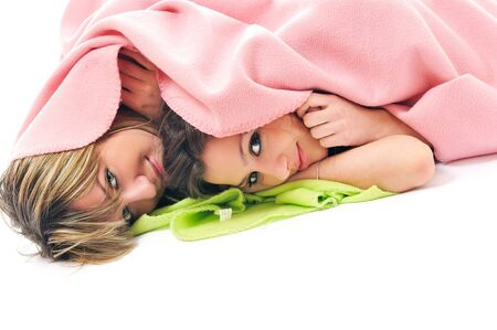 lesbians: two youg happy giril woman smiling unger blanket isolated representing concept of lesbian love, happynes and softnes Stock Photo