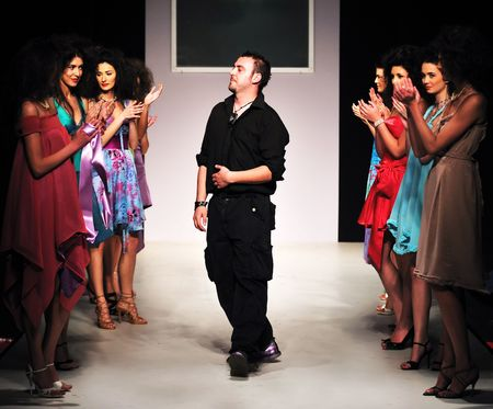 runway fashion: young successful fashion designer on the end of fashion show