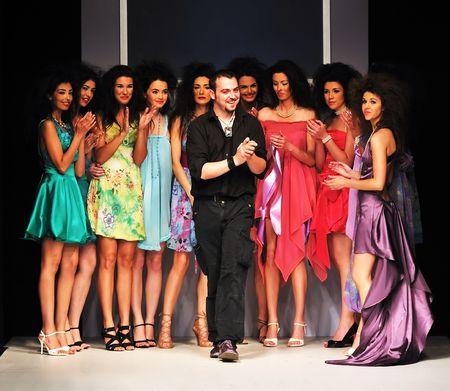 modelo en pasarela: �xito de los j�venes dise�adores de moda en el final del desfile de moda Foto de archivo